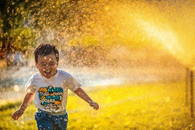 噴水で遊ぶ子供